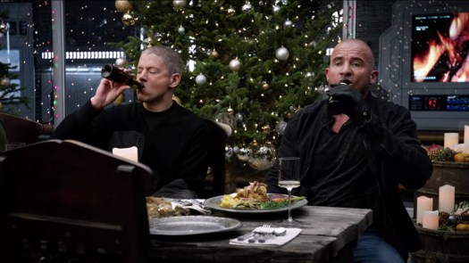 Captain Cold (Wentworth Miller) and Heat Wave (Dominic Purcell) knock back beers at the Christmas dinner table in Legends of Tomorrow.