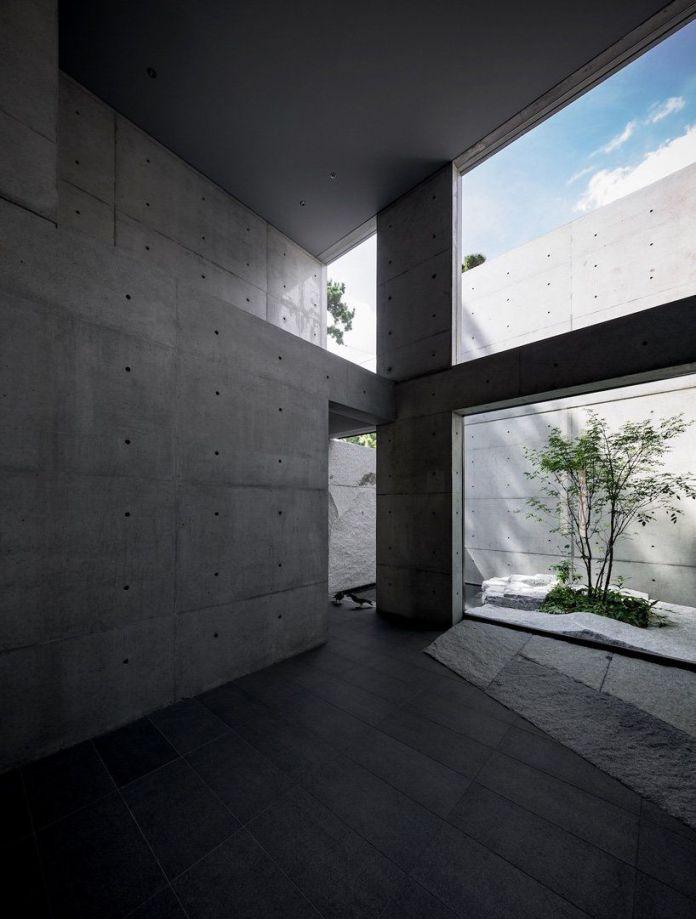 Полностью бетонный номер с высокими потолками и выходом в открытый дзенский сад.