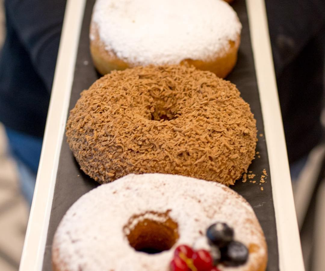 Four donuts of various styles and colors on a tray receding into the background