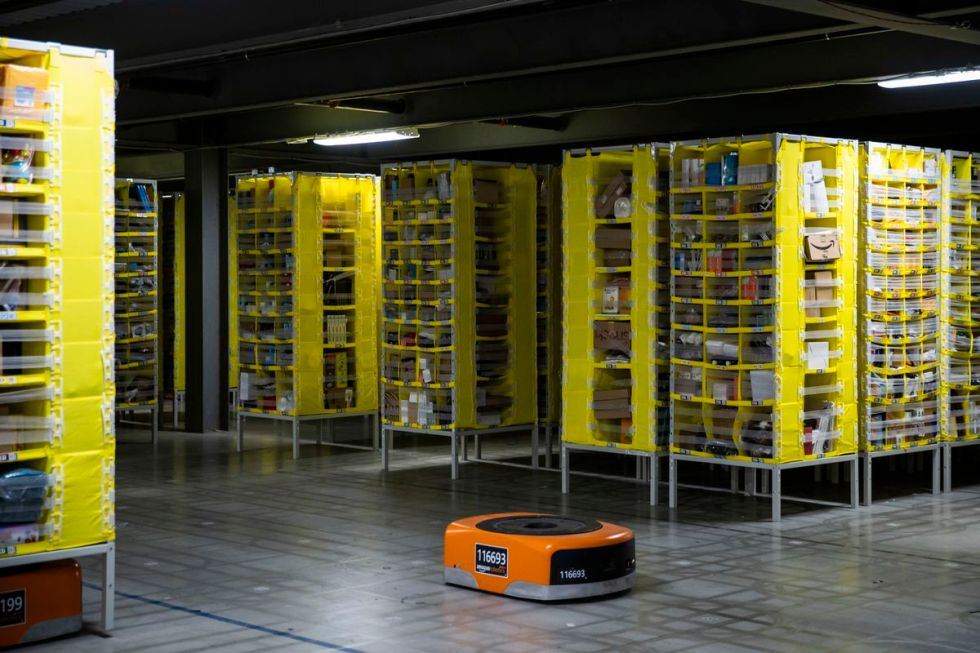 Squat orange robots tuck themselves under the yellow product pods and convey them to the pickers at MDW7 in Monee.