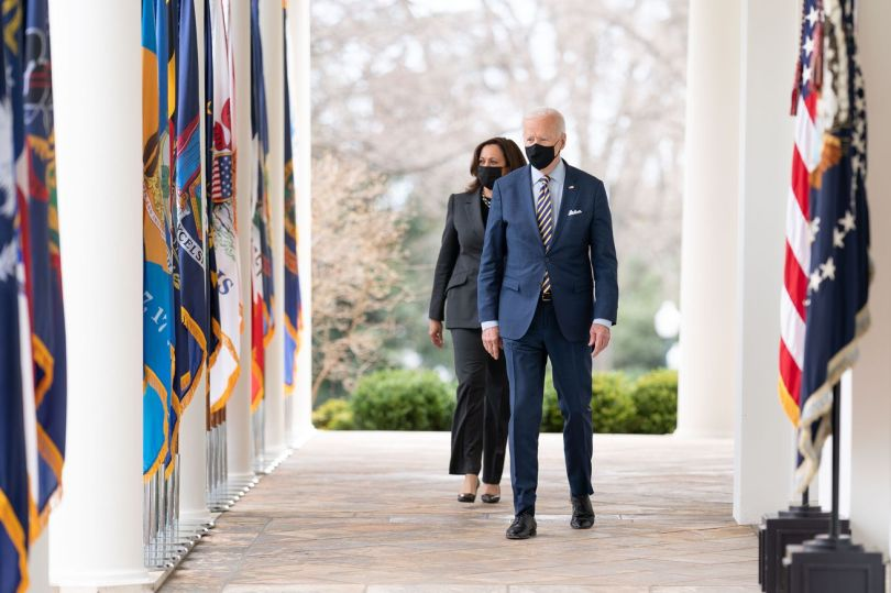 President Joe Biden and Vice President Kamala Harris walk from the Oval Office of the White House, both wearing masks.