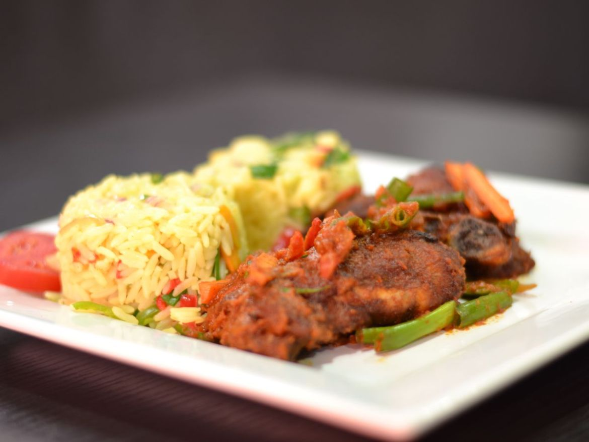 Hunks of meat in a thick sauce sit next to a pile of rice and on a bed of vegetables on a broad white plate