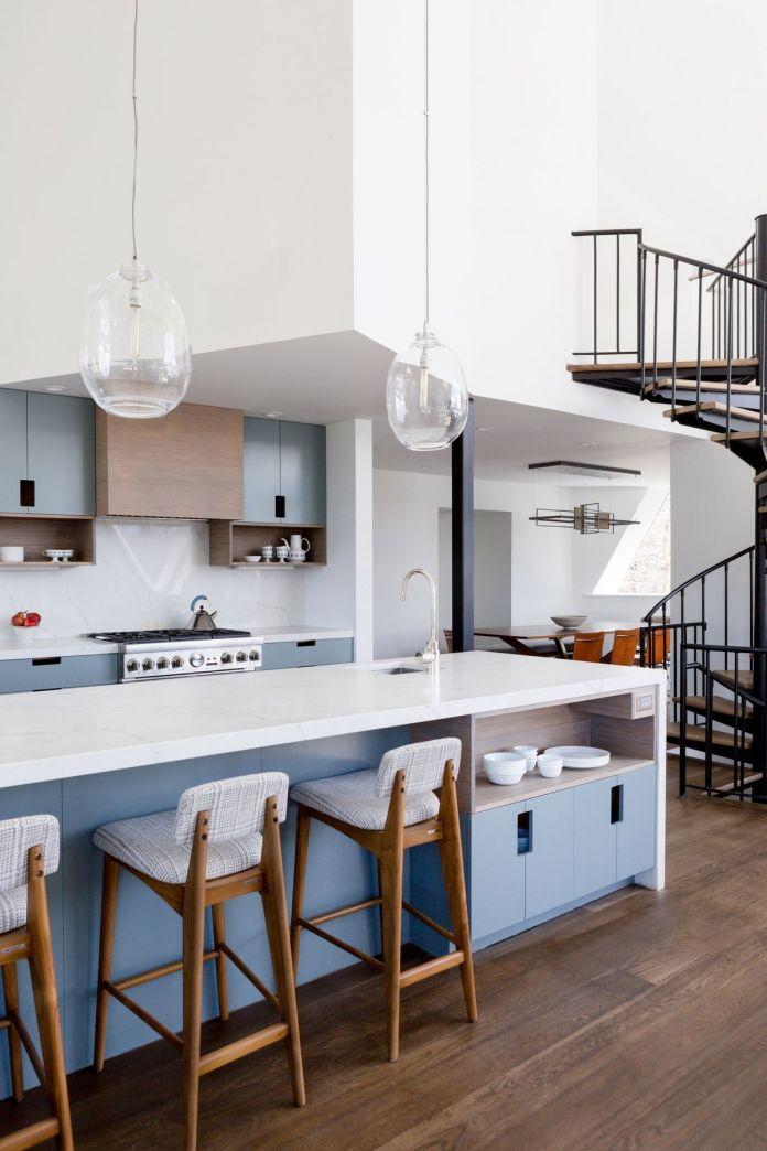 Современная кухня с белыми столешницами и синими шкафчиками находится под высокими потолками и рядом с металлической винтовой лестницей.