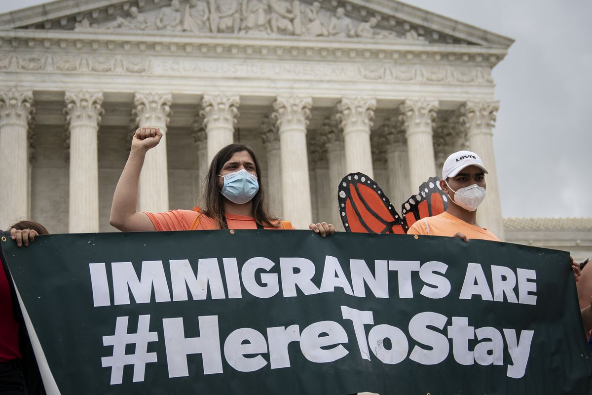 "Protesters in front of the US supreme Court hold a banner that reads ""Immigrants are #HereToStay."""