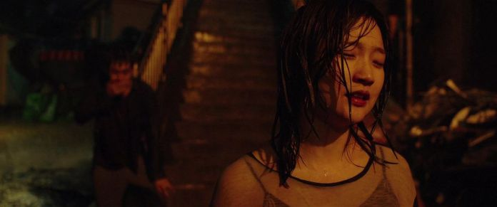 Parasite's Park So-dam stands at the bottom of a staircase, soaking wet and with her hair curling around her face, as her brother stands behind her, hand over his mouth in shock.