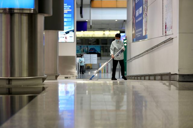 Cleaner wearing mask while cleaning at the Hong Kong Airport...