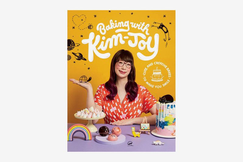 "The cover of ""Baking with Kim-Joy"" featuring Kim Joy posing with a table full of baked goods"