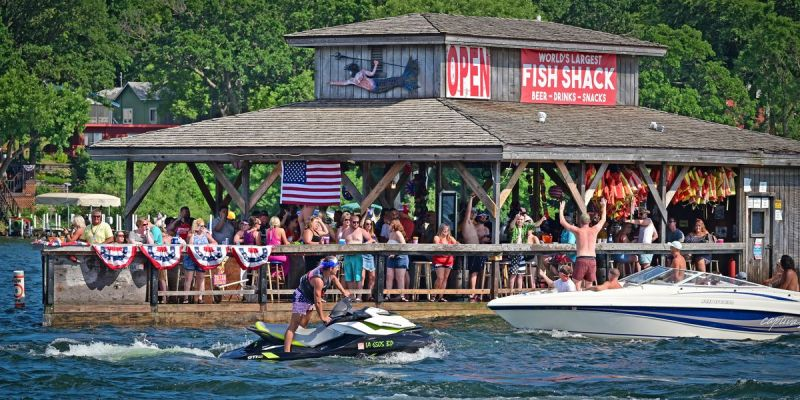 A person on a Jet Ski and people on a motorboat move past a crowded restaurant-bar built on a water-level pier on the lake.