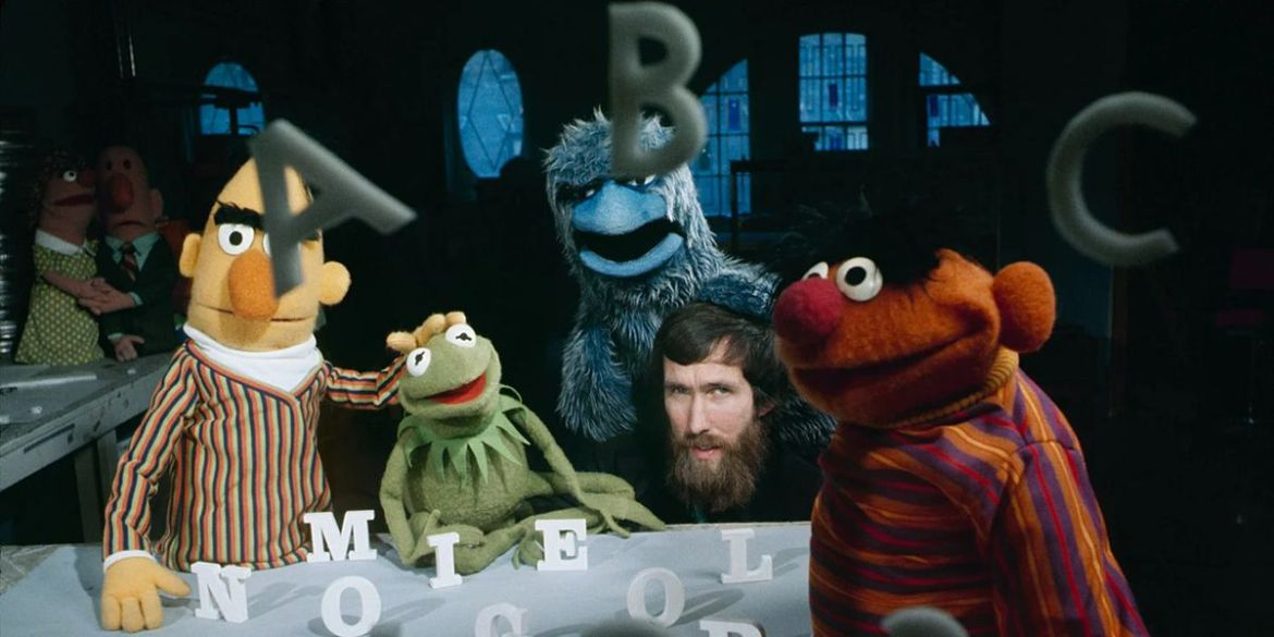 A young, bearded Jim Henson behind the scenes of a Sesame Street skit