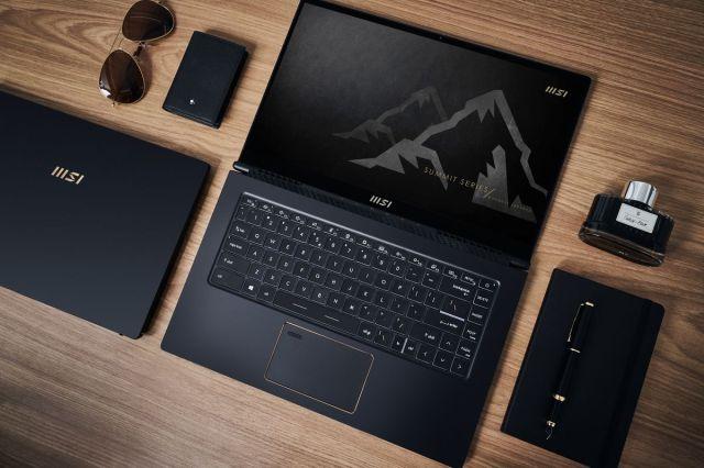 An MSI Summit Series laptop open flat on a desk, alongside other black accessories.