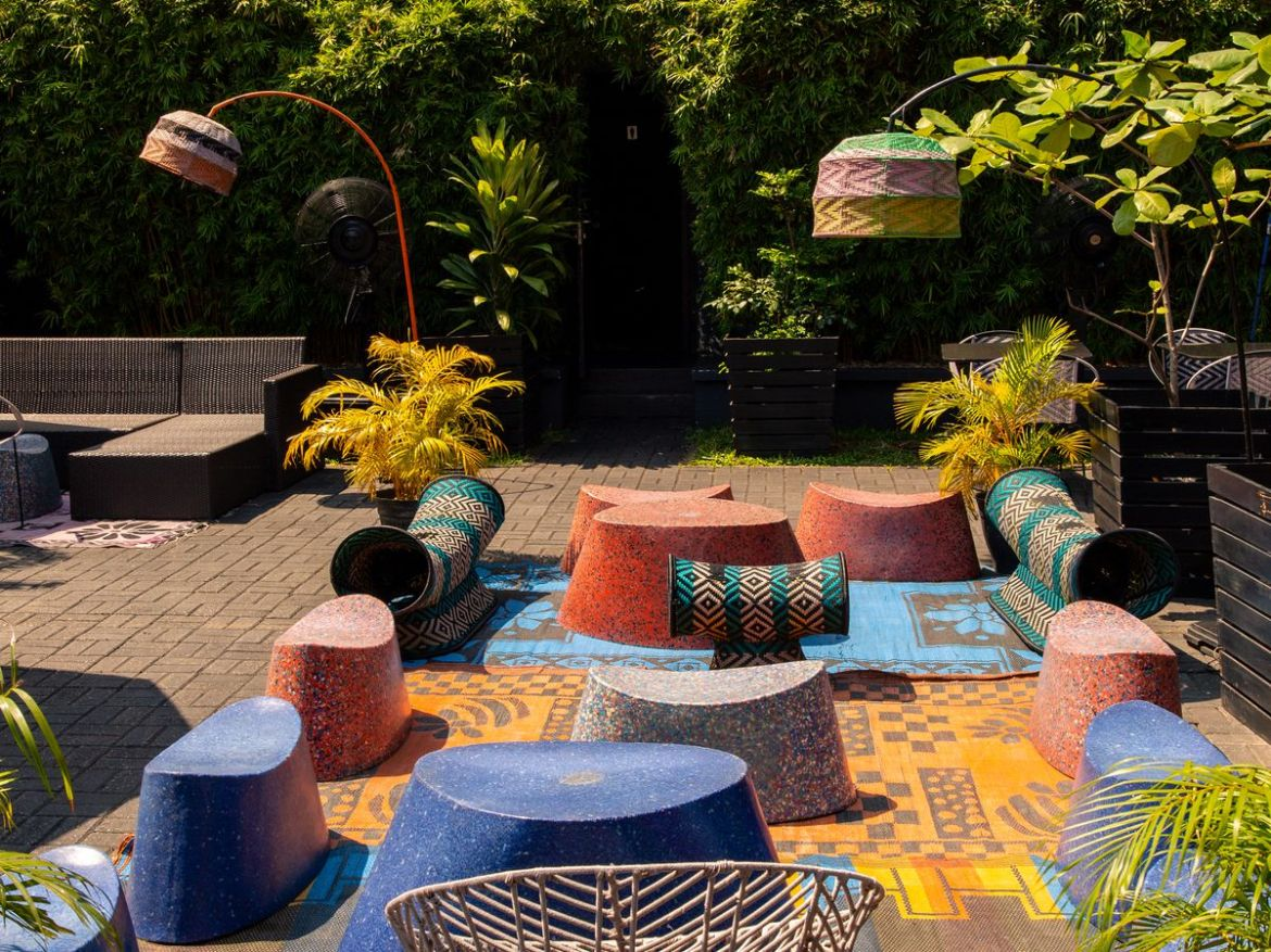 A sunny patio surrounded by large hedges, with small colorful varied seating options on a colorful patchwork of blankets with arc lamps nearby