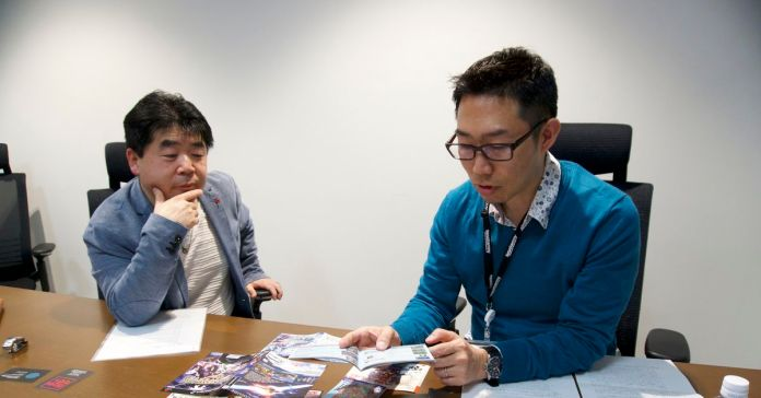 Two game developers look over a table covered in different versions of Phantasy Star Online