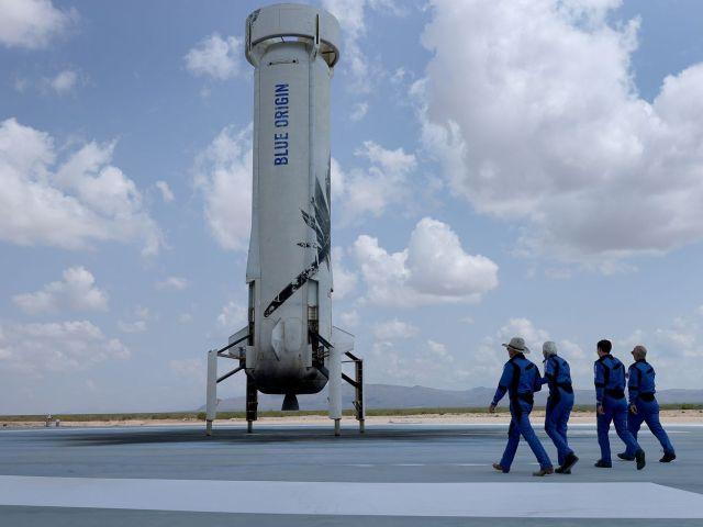 Jeff Bezos, Wally Funk, Oliver Daemen en Mark Bezos van Blue Origin's New Shepard lopen in de buurt van de hulpraket om te poseren voor een foto na hun vlucht in de ruimte.