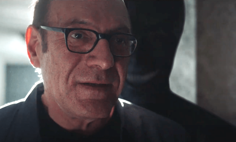A dark figure with a leering smiling stands behind an unsuspecting man looking off-screen.