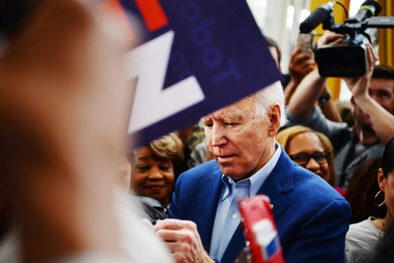 Biden appears to sign an autograph as supporters around him smile; his face is partially obscured by a Biden 2020 sign.