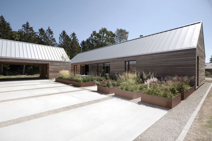 В открытом внутреннем дворе есть ряд прямолинейных кашпо с цветами и травой.