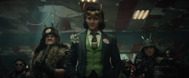 Tom Hiddleston as Loki, dressed in a ragged suit with a VOTE LOKI lapel pin, in Loki (Disney Plus)