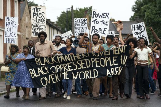 A large group of Black protestors carry a Black Panther banner in Steve McQueen's Small Axe series movie Mangrove