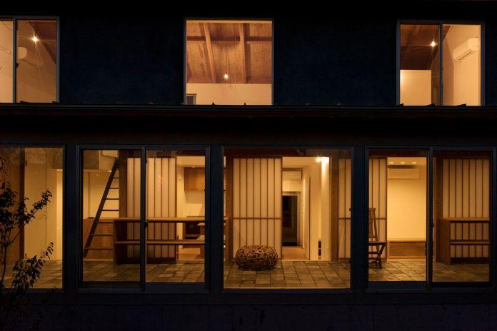 Внешний вид дома ночью, с теплым светом, идущим из всех комнат.