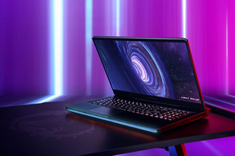 """The MSI GE76 Raider open, angled to the left on a black table with a purple background. The LED strip and keyboard are illuminated. The screen displays a black hole with the slogan """"Light 'em up"""" in the bottom right corner."""