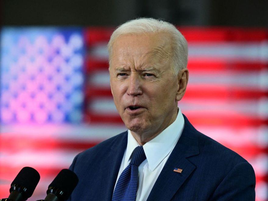 President Joe Biden speaking in front of an American flag backdrop.