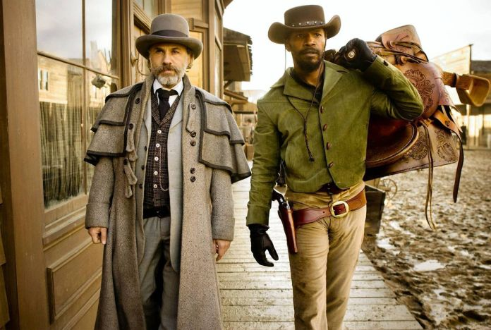 King (Christoph Waltz) and Django (Jamie Foxx) walk down a muddy street in Django Unchained