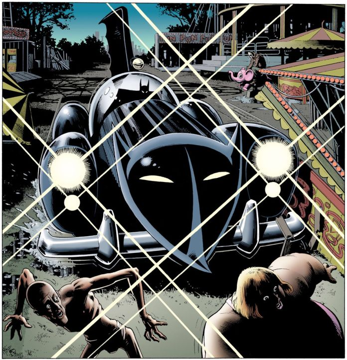 Batman pulls the Batmobile into an abandoned carnival, sending sideshow performers scattering. The car is clearly a modified mid-century roadster, with a big stylized bat-face on the front of it and a huge, scalloped vertical fin sprouting from its back. Seen in Batman: The Killing Joke, DC Comics (1988).