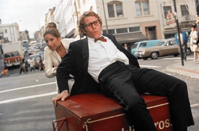 Barbara Streisand pushes Ryan O'Neal down the street in a screenshot from What's Up Doc?