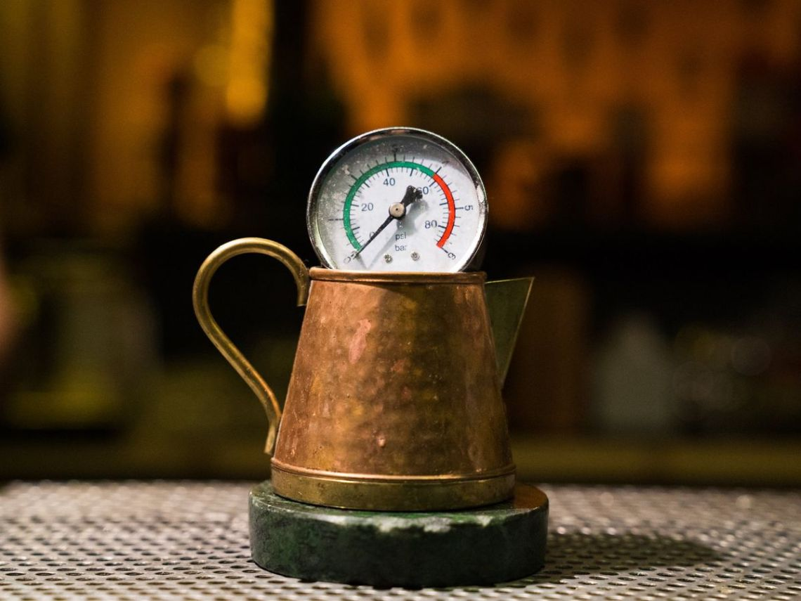 A copper saucer sits on a coaster with a pressure gauge sitting across the rim in a darkened bar setting