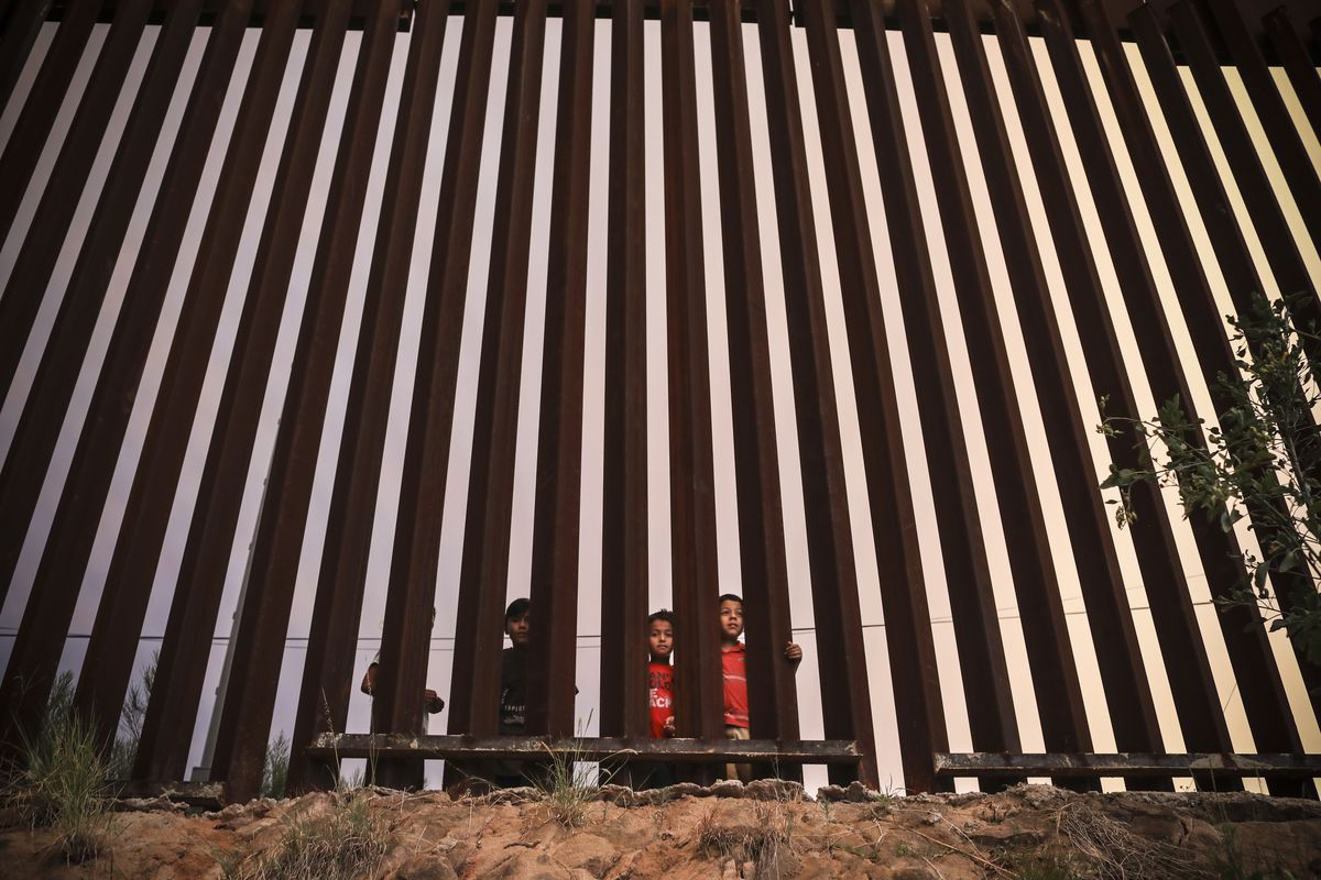 Children look from the Mexican side of the U.S.-Mexico border fence at dusk on July 22, 2018, in Nogales, Arizona.