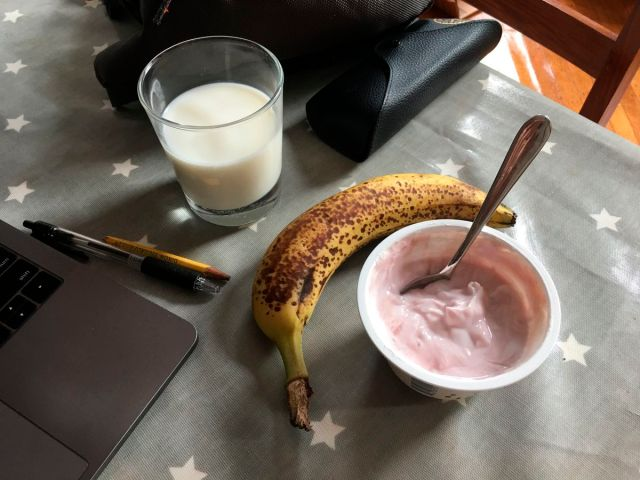 This July 31, 2019 photo shows a yogurt and a banana with a glass of milk on a table in the Brooklyn borough of New York. Even kids who don't want a full breakfast on school mornings may have room for a quick cup of yogurt and a piece of fresh fruit. Meli