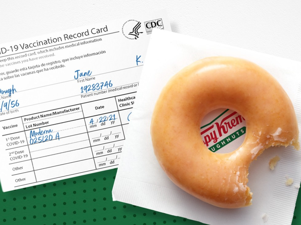 "A glazed donut with a bite taken out of it sits on top of a Krispy Kreme napkin and a COVID-19 vaccination card filled out with the name ""Jane Dough."""