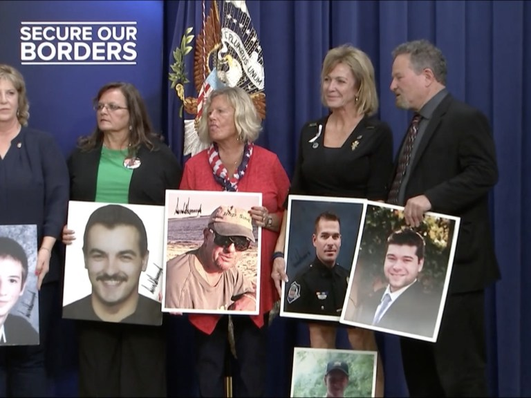Family members hold up images of their loved ones at a White House event.