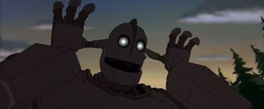 A giant grey robot with glowing yellow eyes makes a silly, goofy face, waving his hands up near his head.