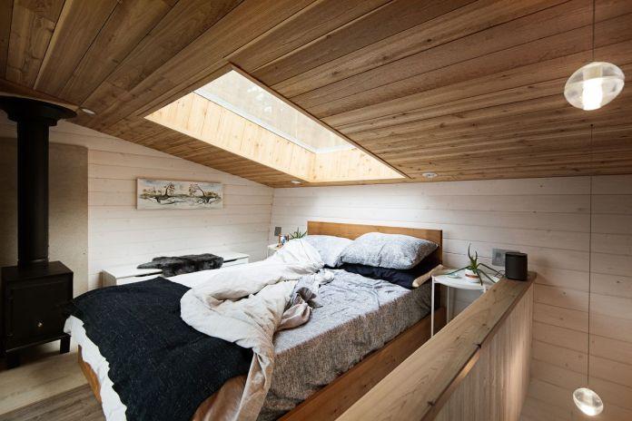 Лофтовая спальня с деревянным потолком и потолочным окном наверху. В углу стоит дровяная печь.
