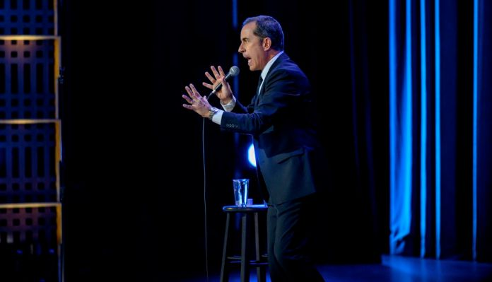 Jerry Seinfeld stands on stage, seen in profile, hands spread apart as he grimaces.