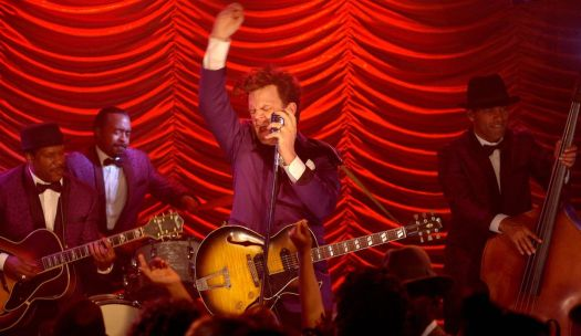 John C. Reilly performs in front of a red curtain and a backing band in Walk Hard