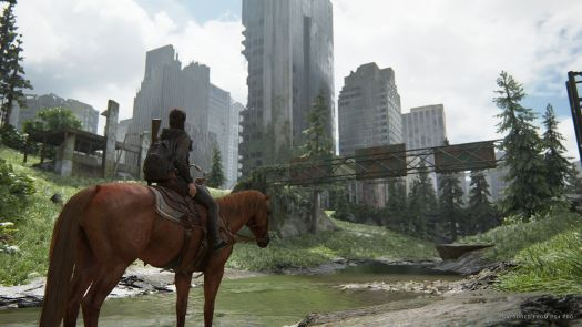 Ellie, on horseback, standing outside a city overtaken by nature in The Last of Us Part 2