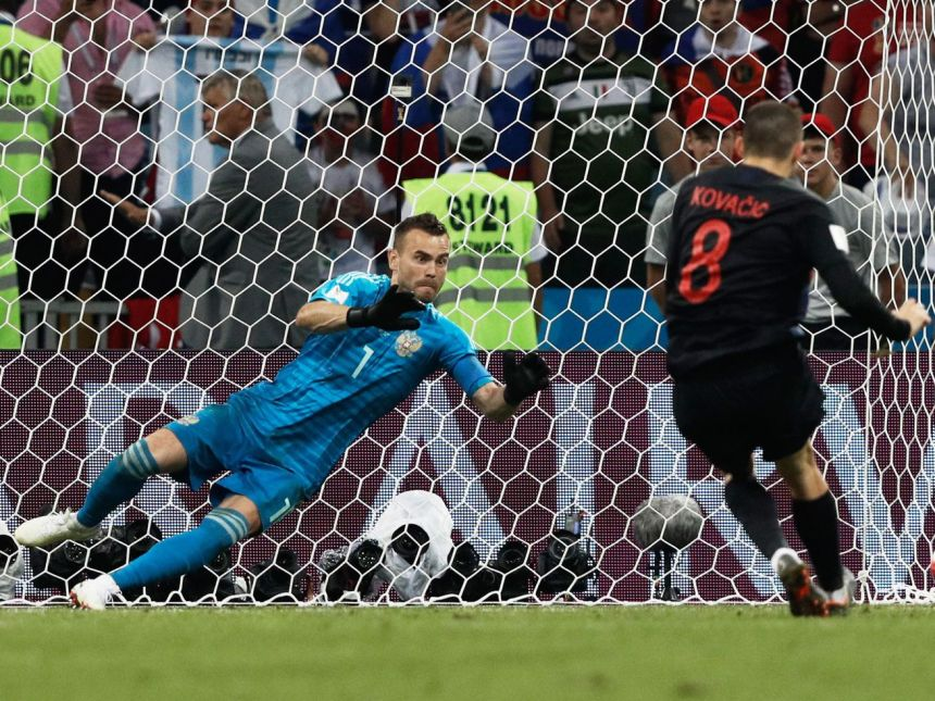 Russian goalkeeper Igor Akinfeev dives to save a penalty kick from Croatian midfielder Mateo Kovacic during a World Cup quarterfinal match on July 7, 2018.