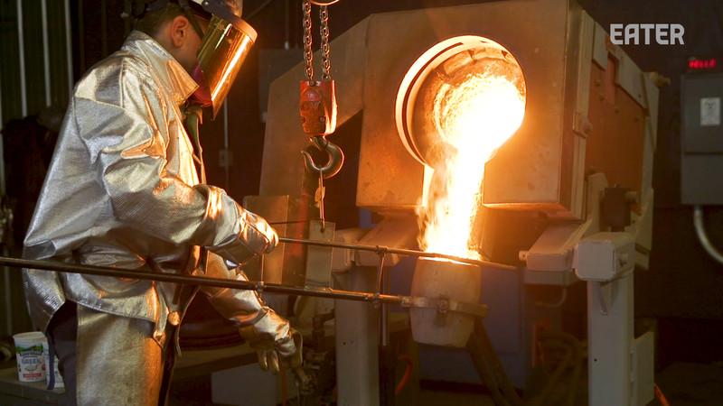 Man pouring molten metal into a mold