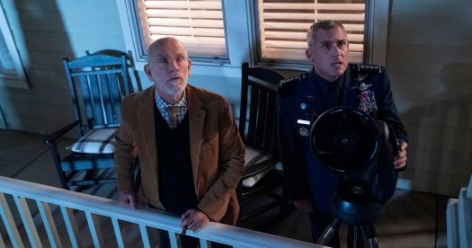 John Malkovich and Steve Carell stand on an exterior porch, staring upward in shock, in Space Force