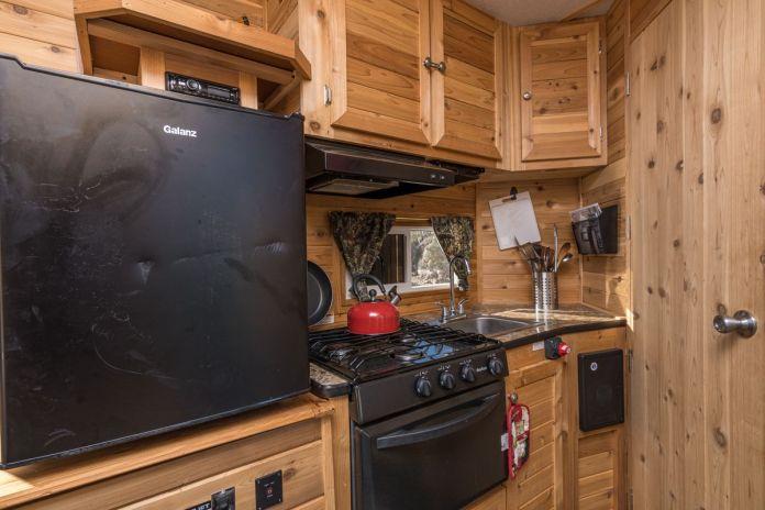 Кухня-камбуз располагает черным холодильником, плитой и духовкой, деревянными панелями на стенах и деревянными шкафами.