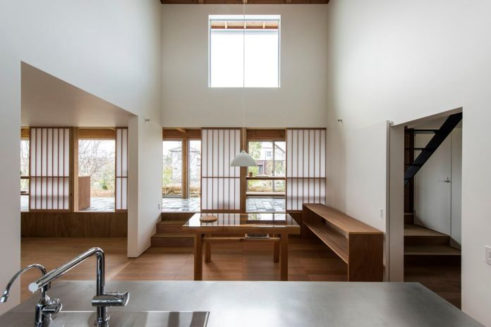 Открытая столовая с высокими потолками, деревянным буфетом и столом, а также выход на каменную террасу.