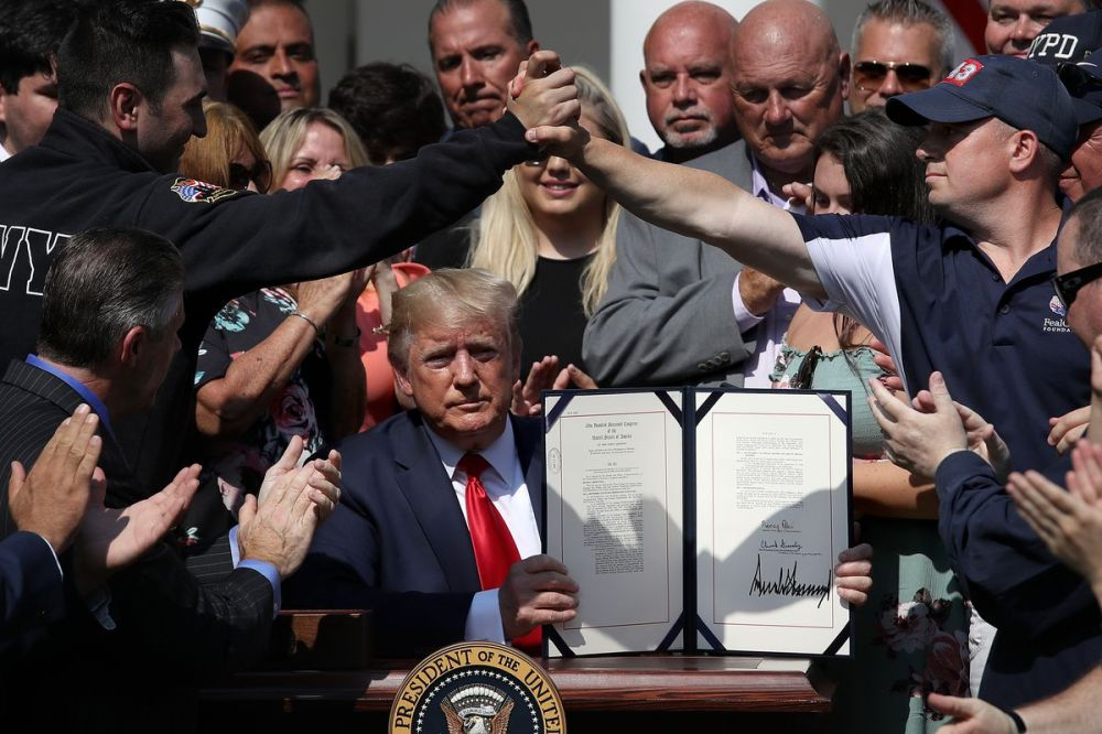 As first responders and their families celebrate, U.S. President Donald Trump shows off his signature on H.R. 1327, an act to permanently authorize the September 11th victim compensation fund, in the Rose Garden of the White House July 29, 2019 in Washing