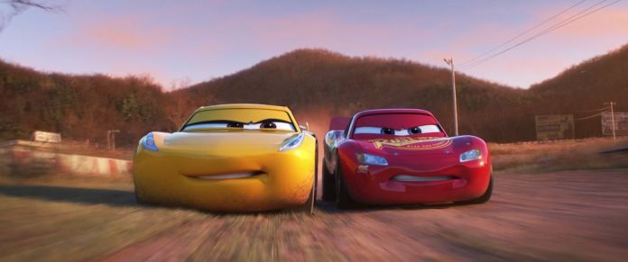 a yellow racecar with a face next to a red racecar with a face, jostling for position on a track