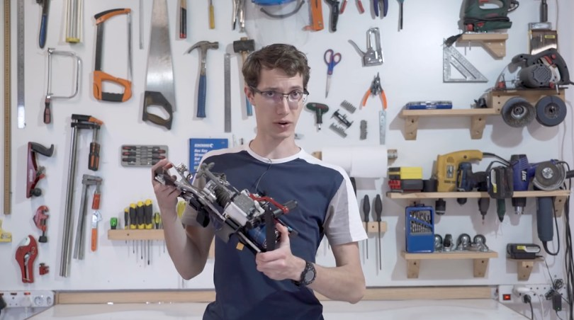Screenshot of JT holding his grappling hook device