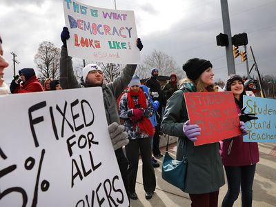 West Virginia teachers, students and supporters hold signs on a Morgantown street as they continue their strike on March 2, 2018.