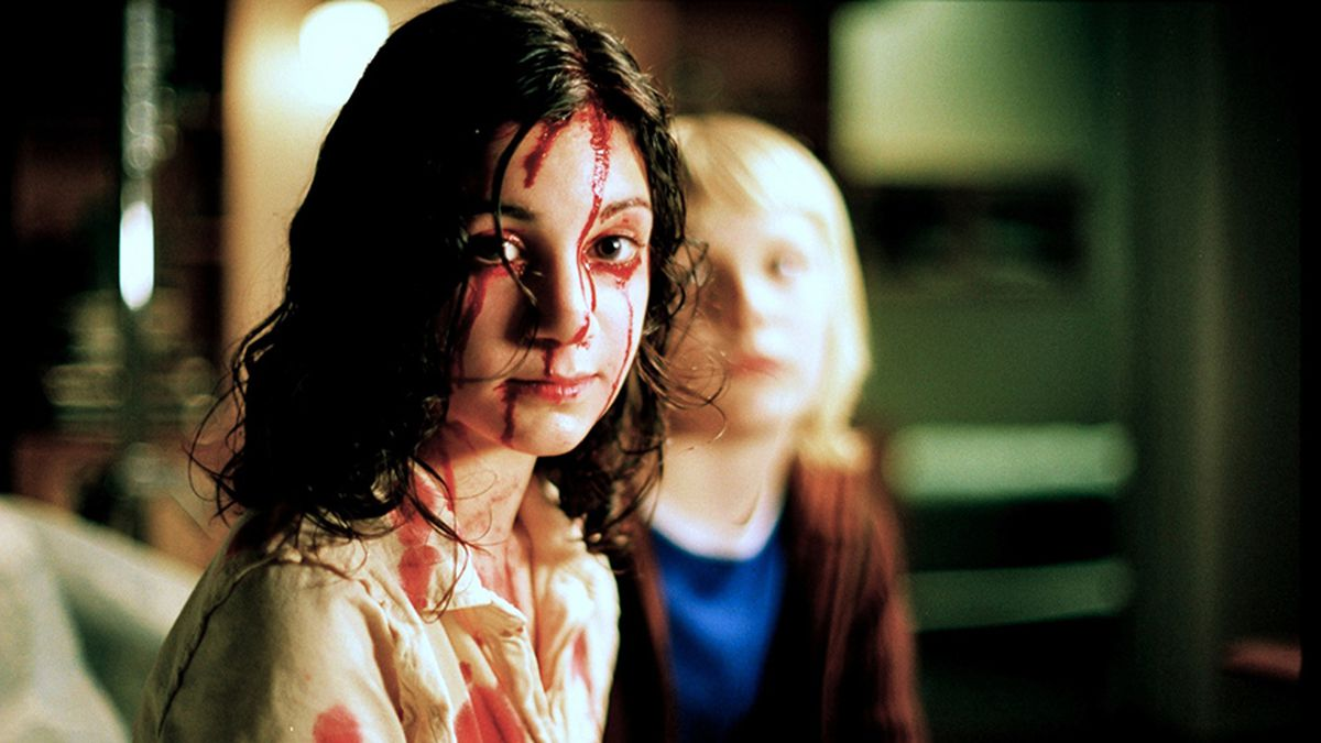 Lina Leandersson, a dark-haired little girl with wide eyes, sits covered in blood in Let the Right One In.