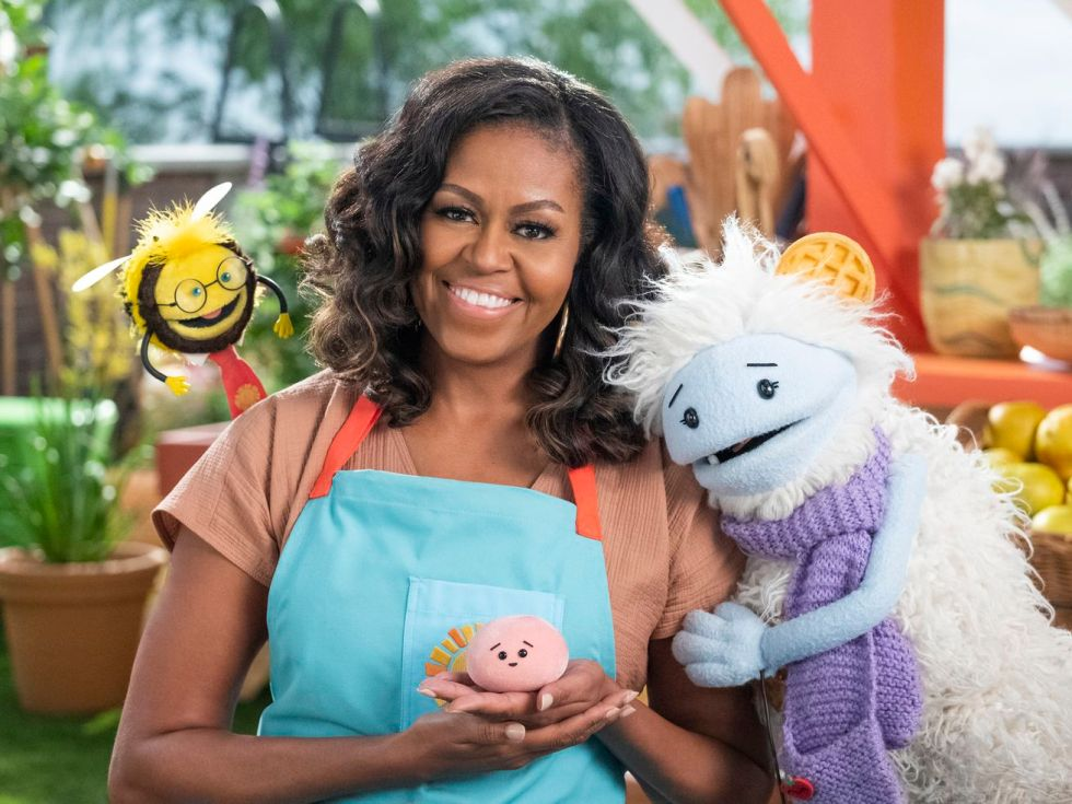Michelle Obama smiling and surrounded by a puppet bee, a yeti-like puppet, and a little mochi stuffie in her hands.
