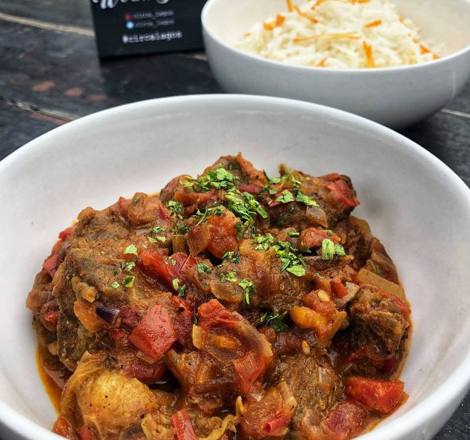 A white bowl of thick meaty curry with tomatoes, potatoes and chunks of meat visible and diced greens for garnish, on a wooden table with another bowl of food blurred in the background